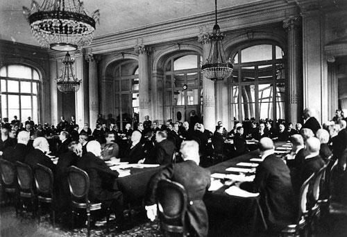 """Bei den Friedensverhandlungen in Versailles, Hotel """"Trianon Palace"""", 7. Mai 1919: Der französische Premierminister Georges Clemenceau (rechts im Bild, stehend) trägt der deutschen Delegation die Bedingungen der Alliierten vor."""