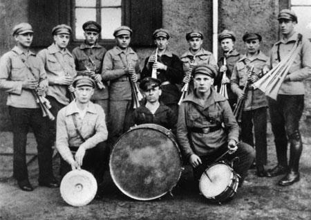 """Vater und Sohn (vorne rechts im Bild) einträchtig nebeneinander: """"Spielmannszug des Roten Frontkämpferbundes in Wiebelskirchen – etwa 1929. Hinter der großen Trommel Wilhelm Honecker, neben ihm sein Sohn Erich."""""""