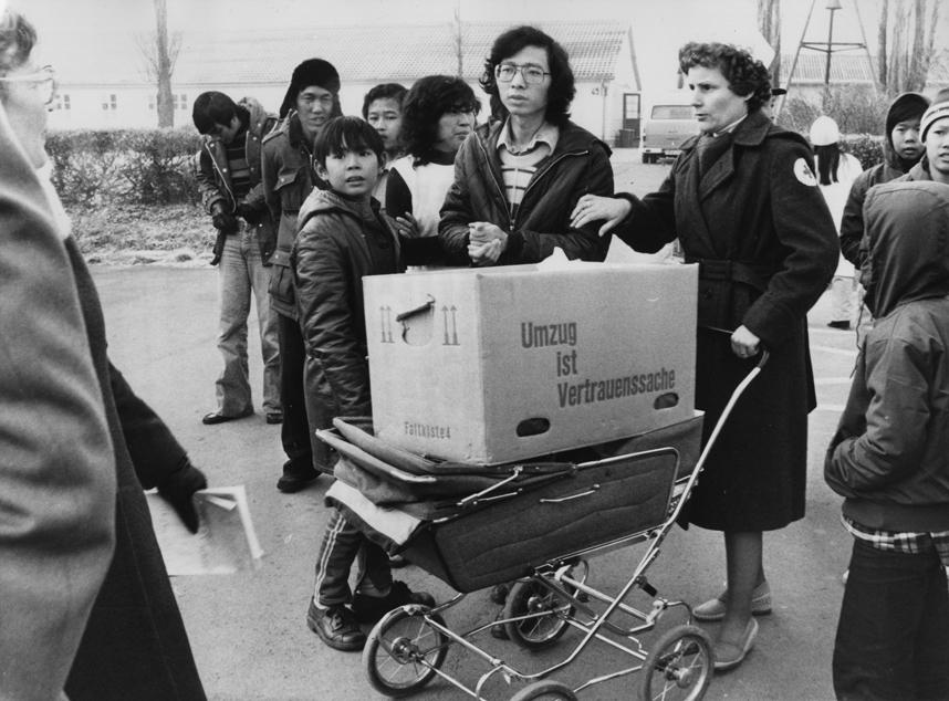 Vietnamesische Flüchtlinge nach ihrer Ankunft im Lager Friedland, 7. Dezember 1978, mit einer Helferin des Roten Kreuzes