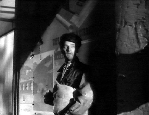 Still from film: The deserter on the run: Simon slips into a sidestreet to avoid detection.