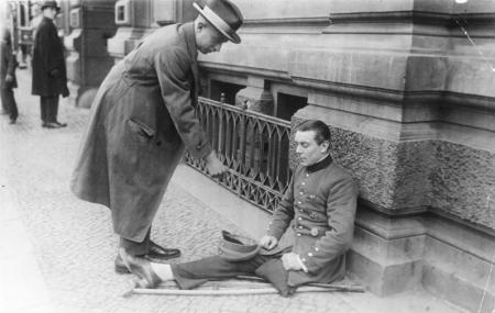 Bettelnder Kriegsversehrter mit »Eisernem Kreuz« und Verwundetenabzeichen